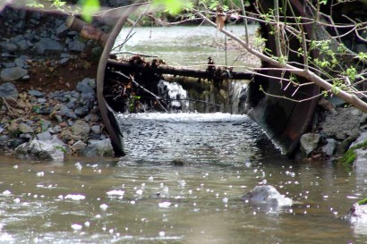 Log blocking water flow through culvert.