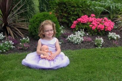 Ellie in front of flowerbed.