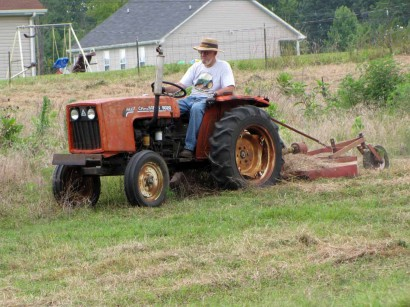 farmer mowing field