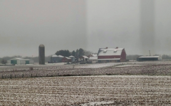 Snow falling on farmland in Illinois.